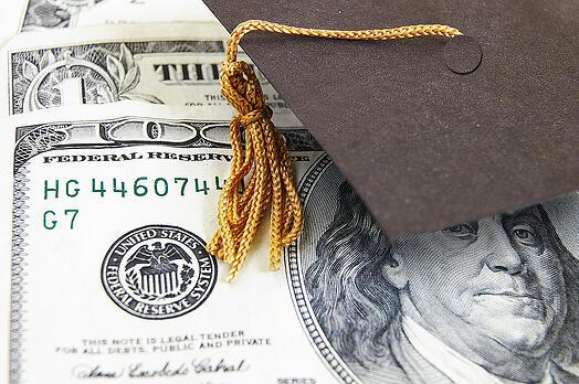bigstock-graduation-cap-on-money-31505735