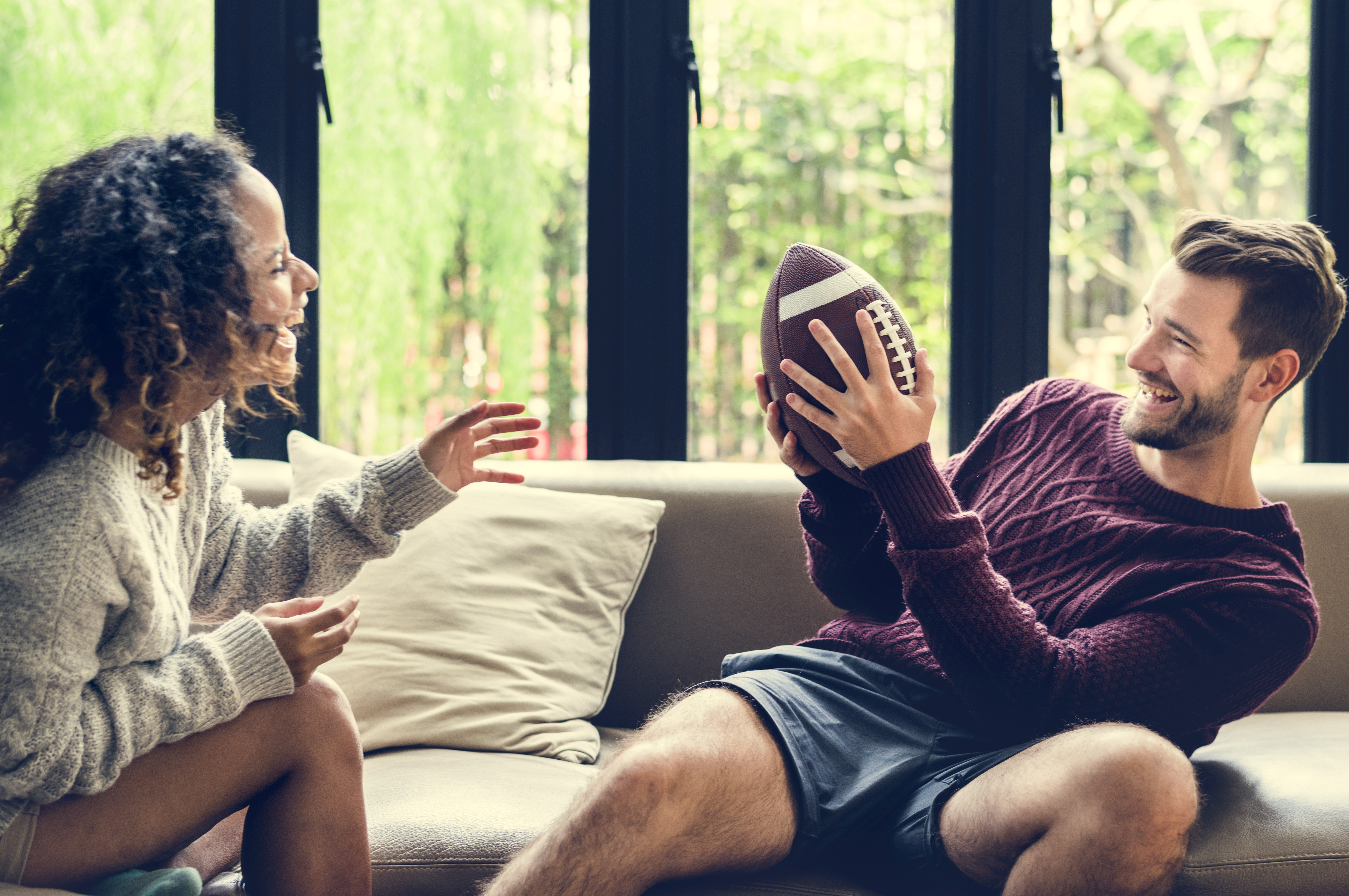 young-couple-watching-american-football-at-home-HGYMA7C
